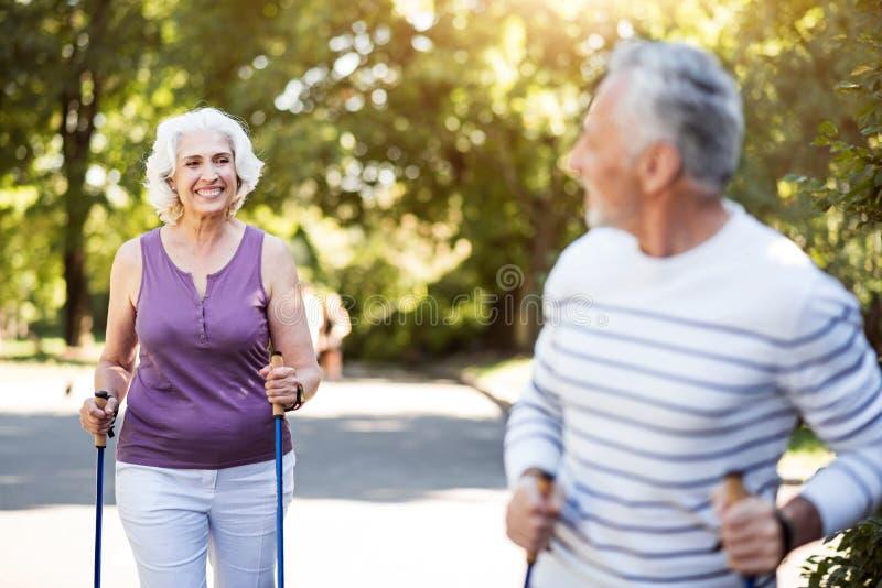 Grå fru för Smiley som ser maken, medan öva in parkera arkivfoton