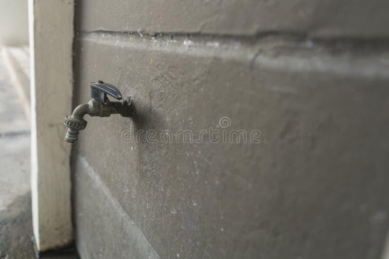 Grå gammal vattenkran på betongväggen royaltyfria bilder