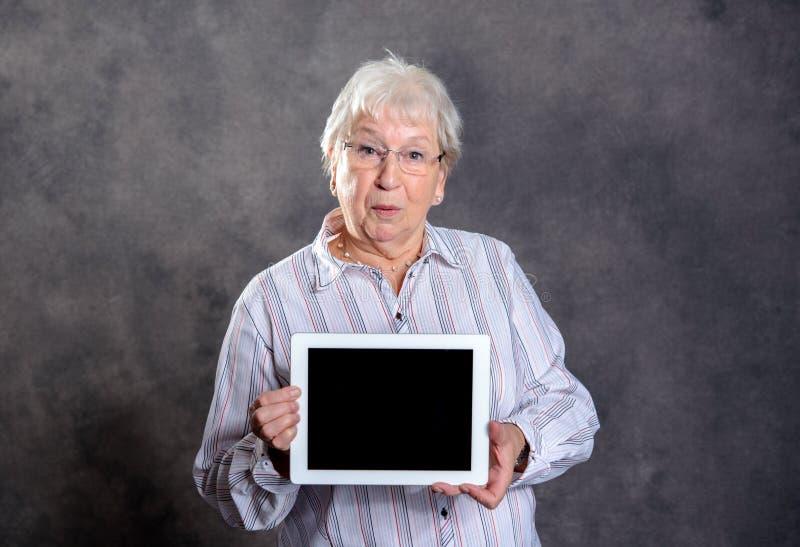 Grå hårig äldre kvinna som använder minnestavlaPC royaltyfri foto