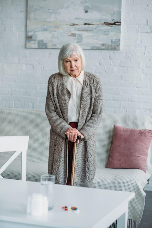 grå hårkvinna med anseende för gå pinne i rum med mediciner på tabletopen arkivbilder