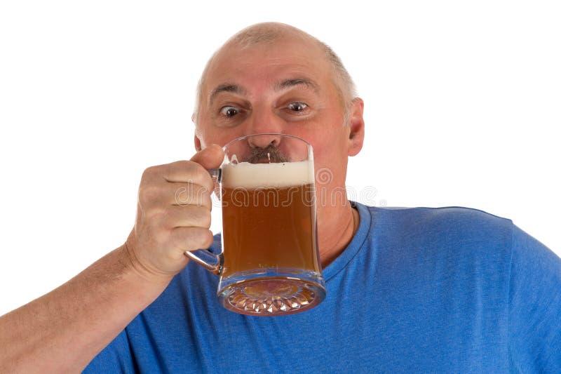 Grå haired man som dricker öl arkivbilder
