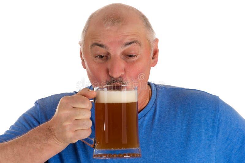 Grå haired man som dricker öl från en råna arkivbilder