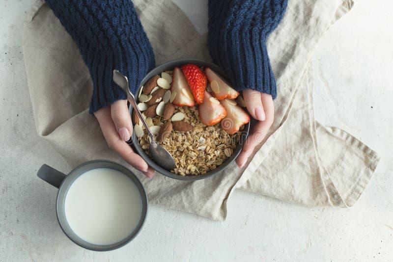 Grå keramisk bunke för sund frukost med granola, jordgubben och muttrar i händer för kvinna` s Banta och det vegetariska matbegre fotografering för bildbyråer