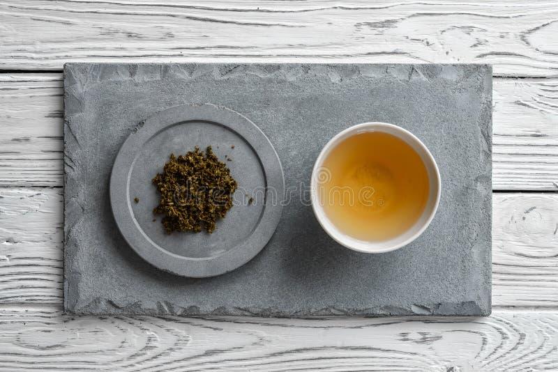 Grå konkret platta på ljus träbakgrund och en kopp te royaltyfri foto