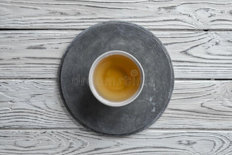 Grå konkret rund platta på ljus träbakgrund och en kopp te arkivfoto