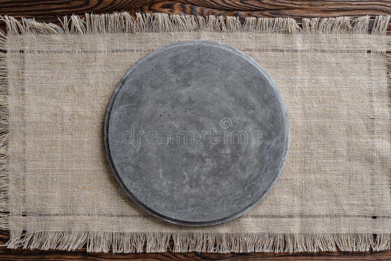 Grå konkret rund skylt på ljust tyg och träbrun bakgrund arkivfoto