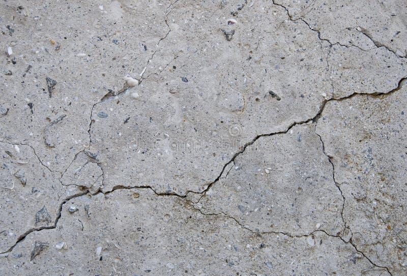 Grå konkret texturbakgrund sprickor skrapor skada Sprucken stenväggbakgrund arkivfoto