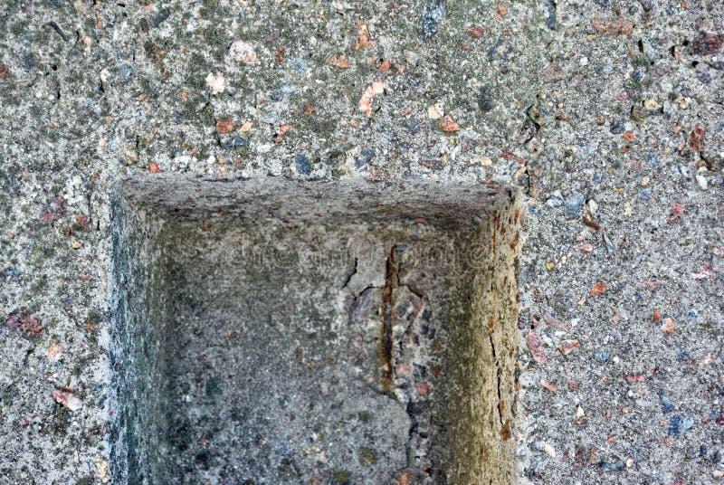 Grå konkret texturvägg med små färgrika stenar med ett fyrkantigt spår fotografering för bildbyråer