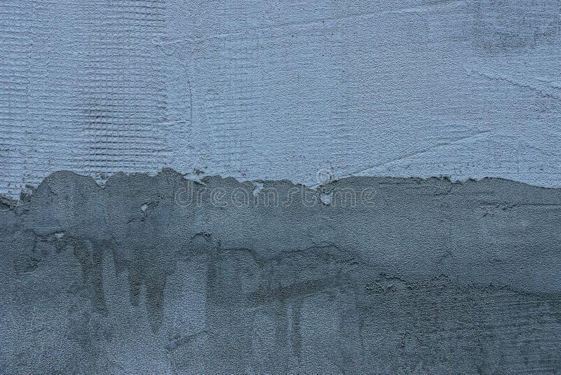 Grå mörk bakgrund från ett fragment av en packad betongvägg arkivbild