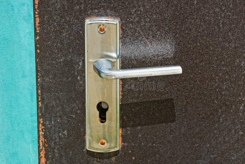 Grå metalldörrknopp på en brun järndörr fotografering för bildbyråer
