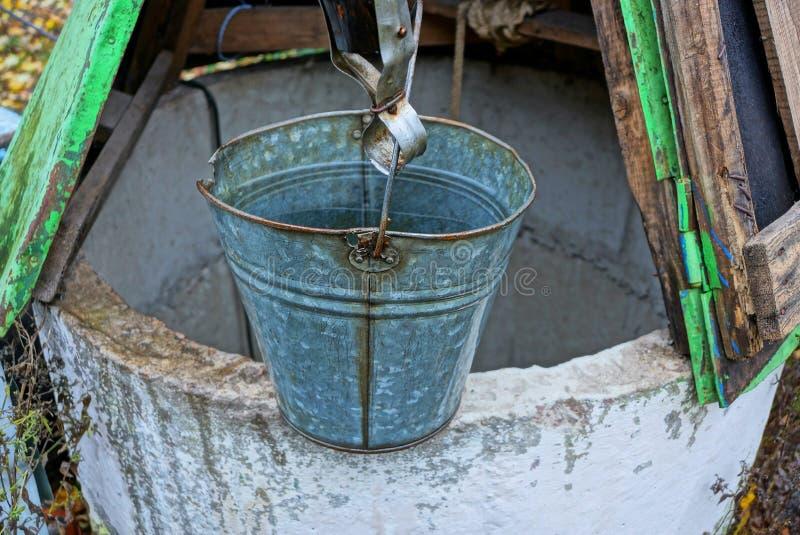 Grå metallhink av vatten som står på en öppen brunn i gatan royaltyfri foto