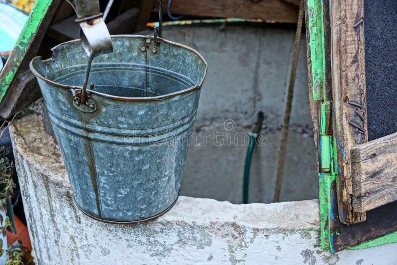 Grå metallhink av vatten som står på en öppen brunn i gatan arkivfoto