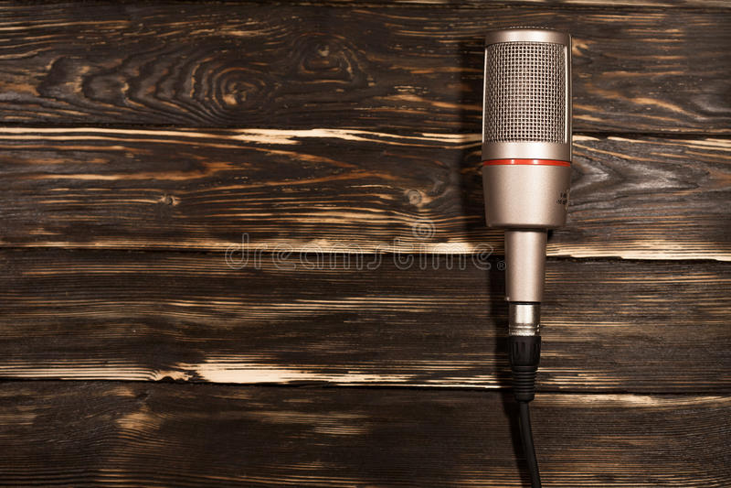 Grå mikrofon på träbakgrund royaltyfria bilder