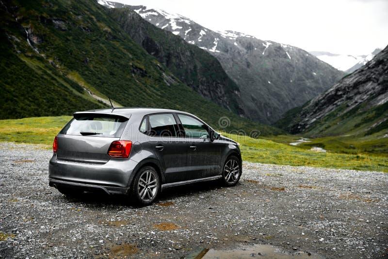 Grå modern bilparkering på en synvinkel i bergen av Norge som vänder mot in mot den gröna dalen royaltyfri fotografi