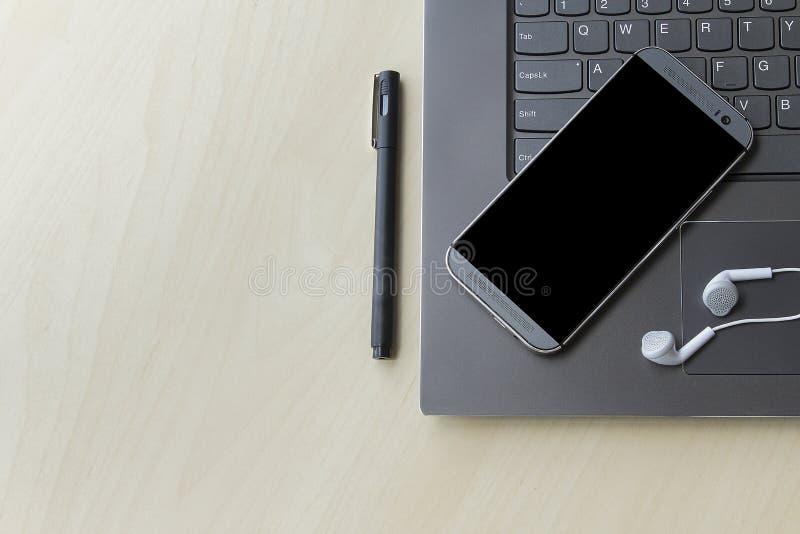 Grå och mörk bärbar dator och mobiltelefon för teknologibegrepp med copyspace royaltyfri bild