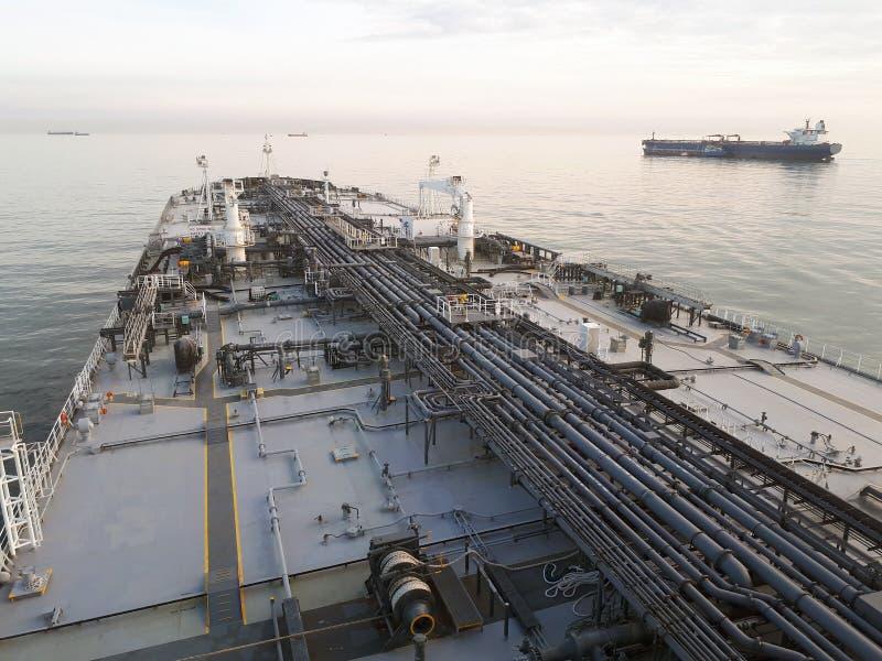 Grå oljetanker på ankarstundsolnedgången royaltyfri foto