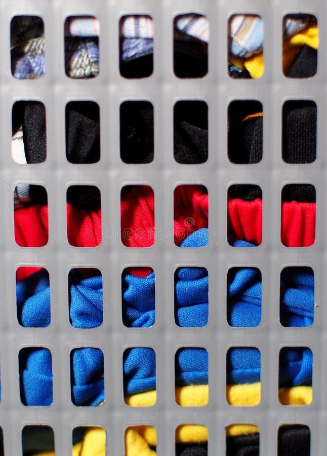 Grå plast- tvättkorg mycket med smutsig färgrik kläder arkivfoton