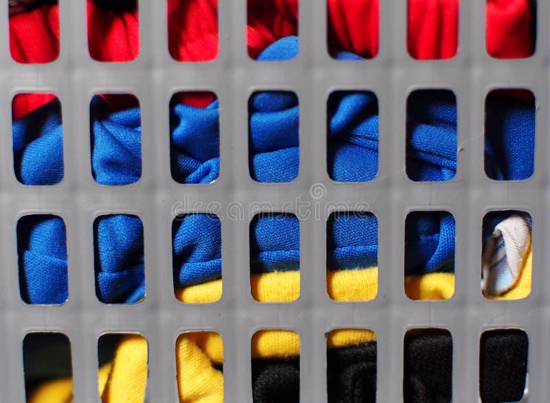 Grå plast- tvättkorg mycket med smutsig färgrik kläder fotografering för bildbyråer