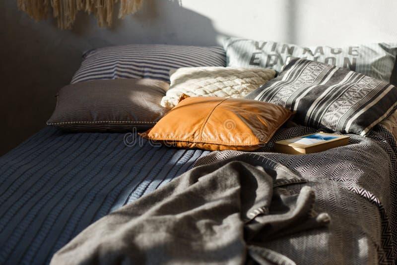 Grå säng, kulöra kuddar och texturerad vägg i bakgrunden Närbildskott, fokus på läderkudden royaltyfria foton