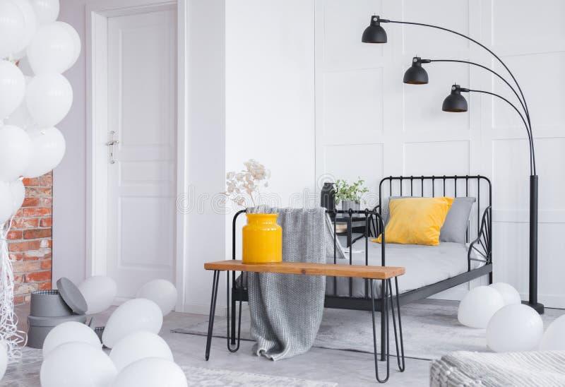 grå säng och gul vas med vita blommor på träbänk i stilfullt industriellt sovrum arkivbild