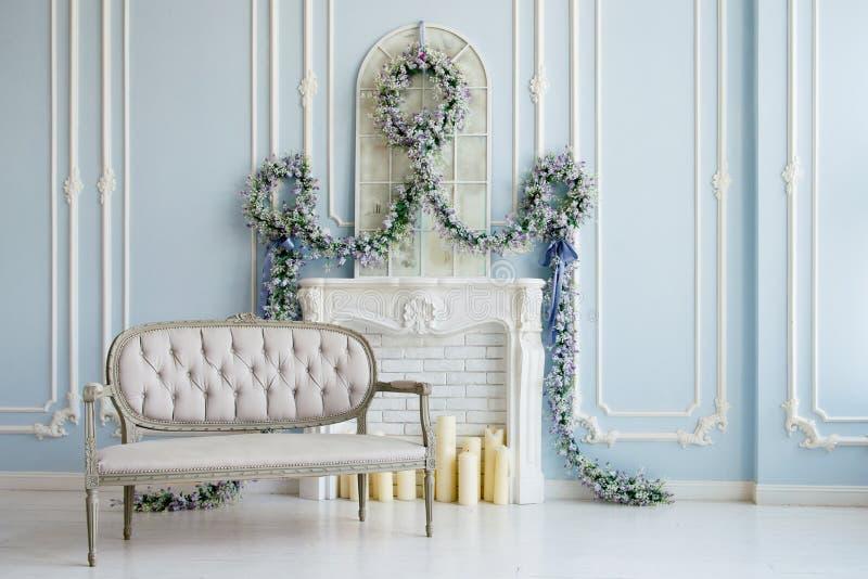 Grå soffa för klassiker i ett lyxigt vitt rum Konstgjord spis på spisen rummet dekoreras med blommor arkivfoto