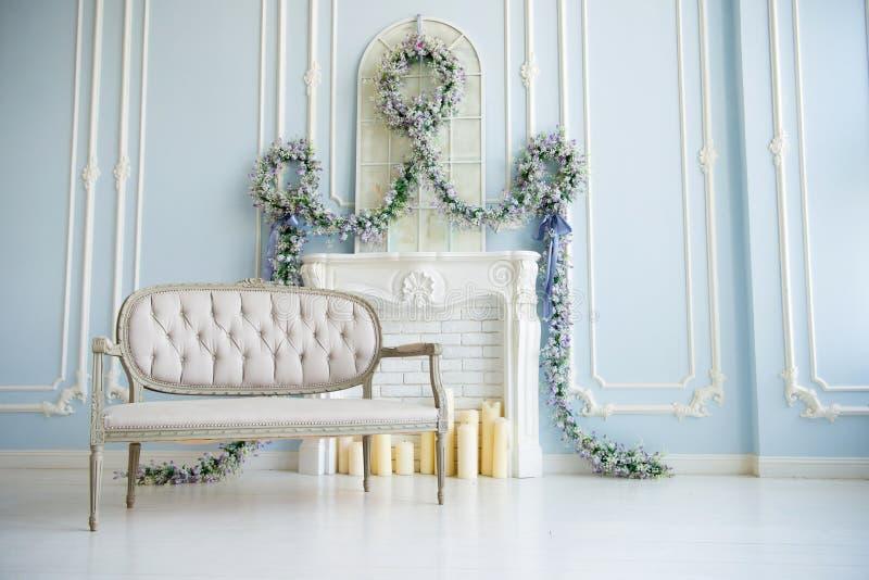 Grå soffa för klassiker i ett lyxigt vitt rum Konstgjord spis på spisen rummet dekoreras med blommor arkivfoton