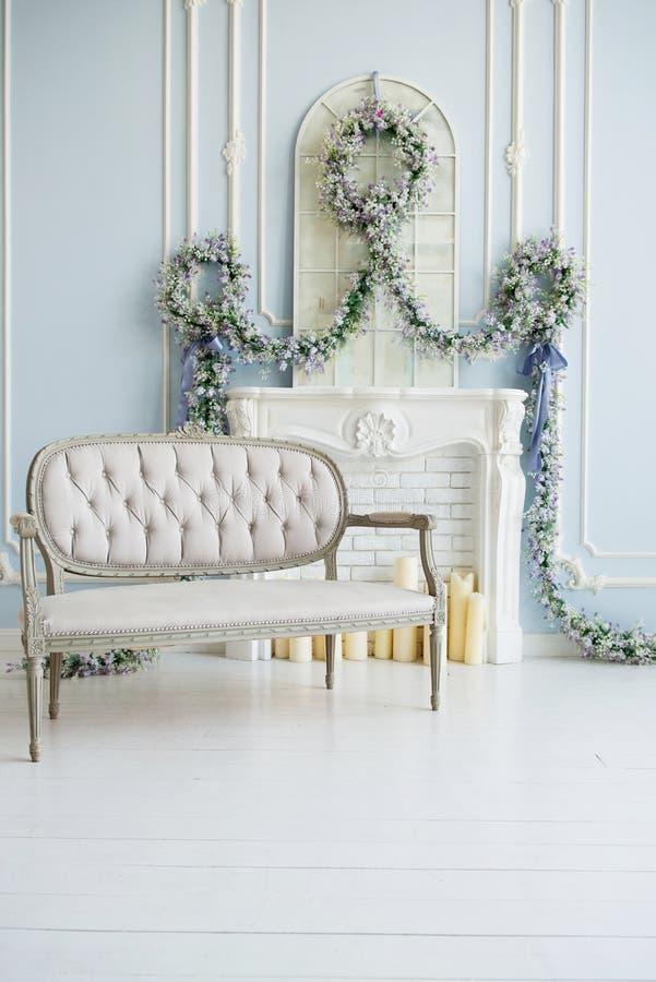 Grå soffa för klassiker i ett lyxigt vitt rum Konstgjord spis på spisen rummet dekoreras med blommor royaltyfri foto