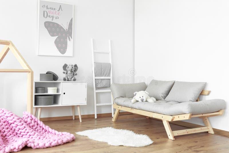 Grå soffa med nallebjörnen royaltyfri foto