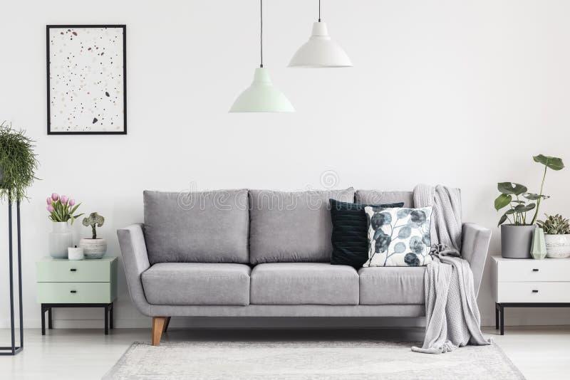 Grå soffa mellan kabinetter med växter i vit vardagsruminte arkivbild