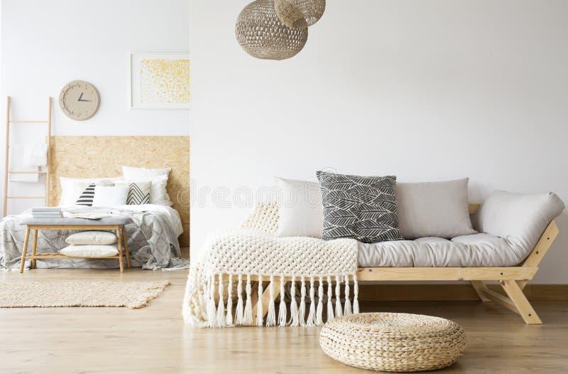 Grå soffa och träsäng royaltyfria foton