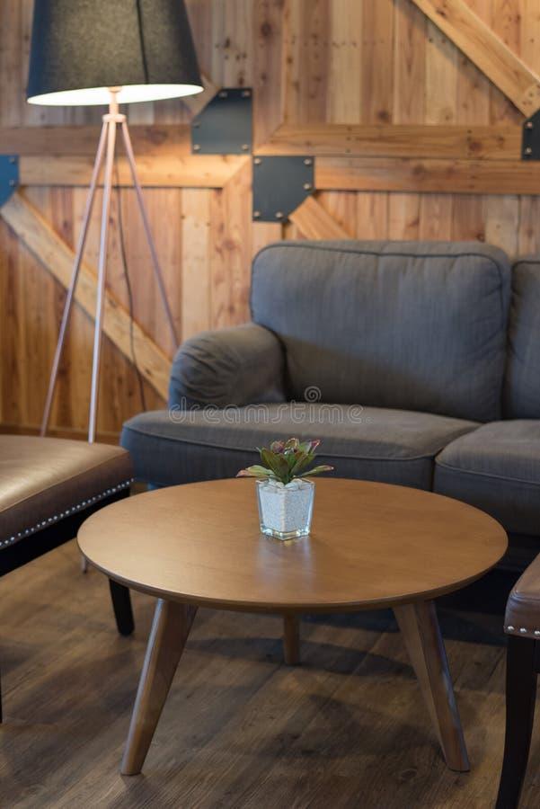 Grå soffa och trätabell i vardagsrum, japansk stil arkivfoton