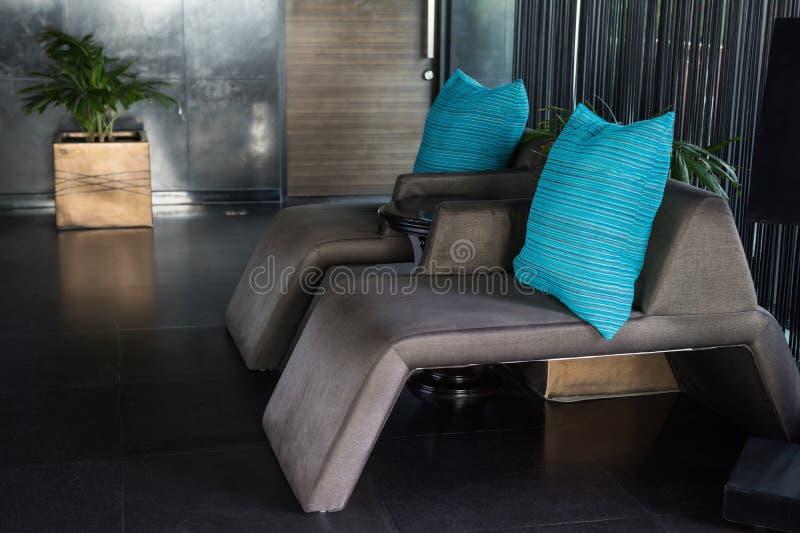 Grå stol för soffasäng i lyxigt hotell royaltyfria bilder