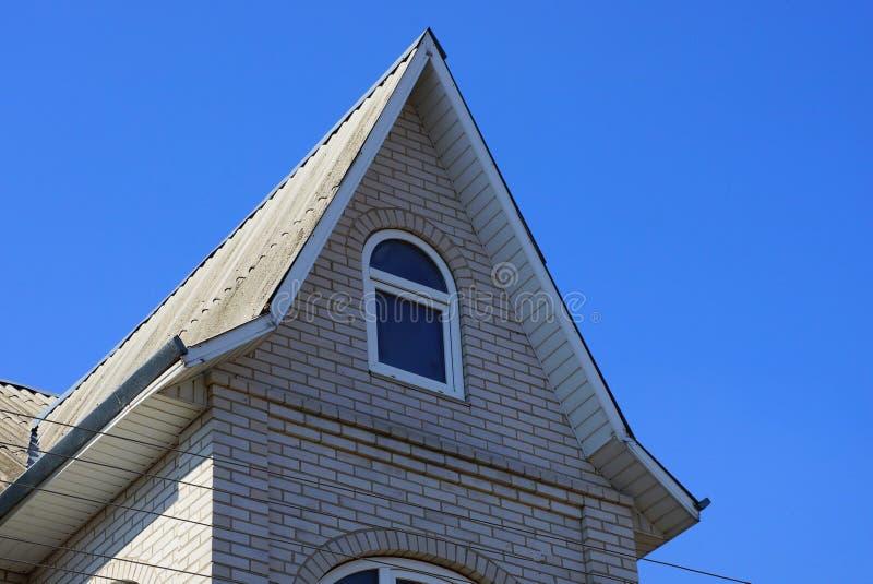 Grå tegelstenloft av ett privat hus med ett fönster mot den blåa himlen royaltyfria bilder