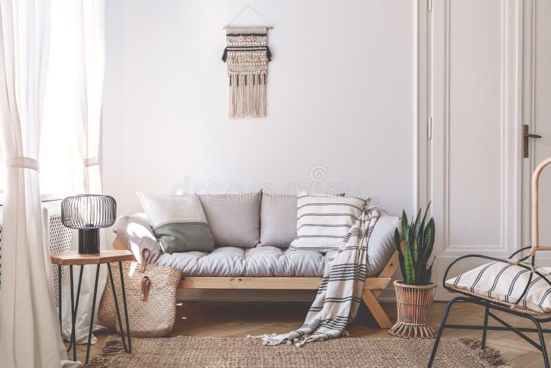 Grå träsoffa med kuddar i den vita vardagsruminre med lampan på tabellen Verkligt foto royaltyfri fotografi