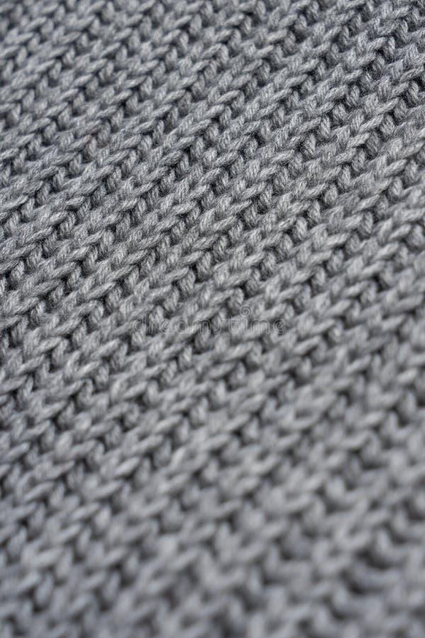 Grå woolen stucken halsduk Closeupsiktstextur med bokeh arkivbild