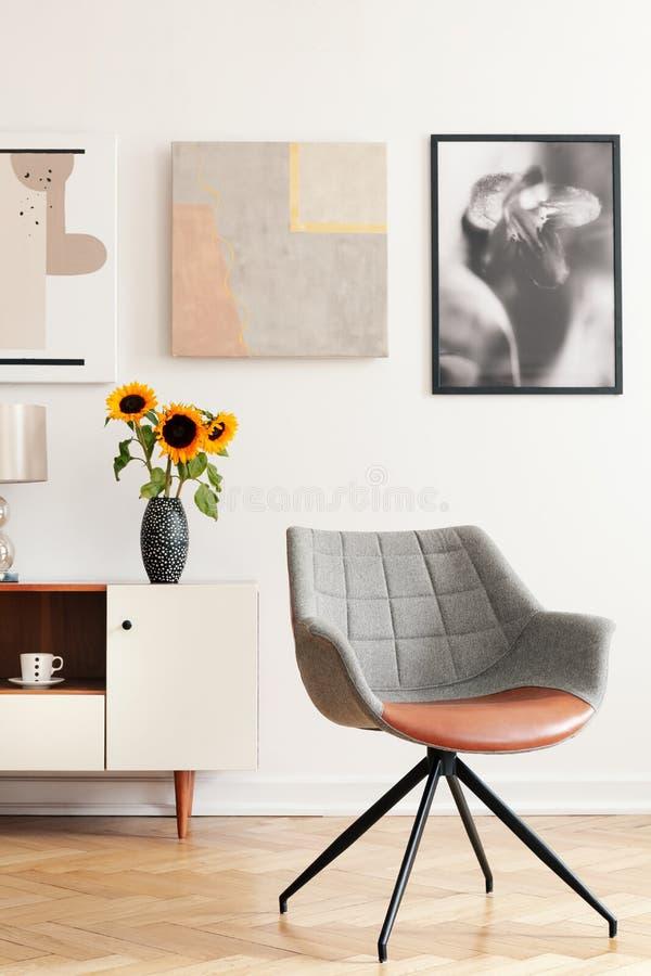 Gråa fåtölj och solrosor på kabinettet i den vita vardagsruminre med affischer arkivfoto