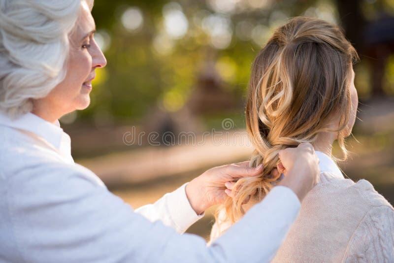 Gråa haired kvinnor som flätar hennes dotterhår royaltyfria foton