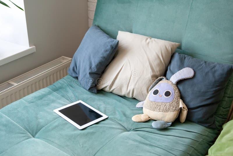 Gråa kuddar, en vit minnestavla och en leksakkanin som ligger på en mjuk, bekväm hemtrevlig grön soffa nära fönstret royaltyfria foton