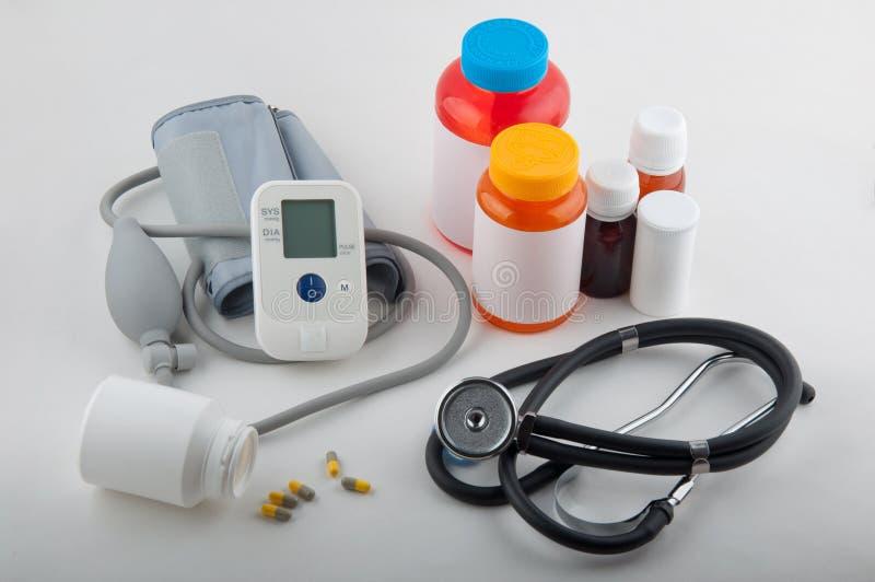 Gråa medicinska tonometer, phonendoscope, preventivpillerar och drogflaskor på vit arkivfoton