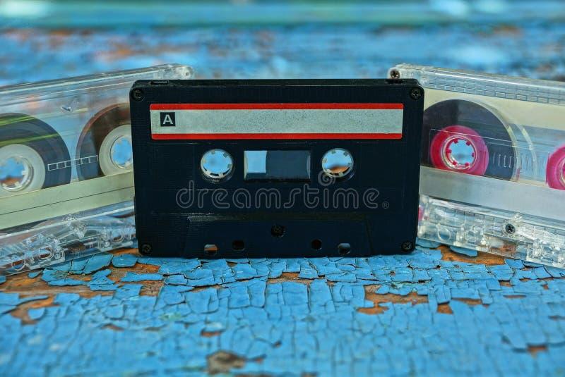 Gråa och svarta gamla ljudband är på det blåa brädet royaltyfria foton