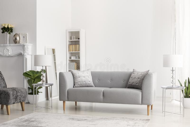 Gråa soffa och lampor på silvertabeller i den vita lägenhetinre med blommor och fåtöljen Verkligt foto royaltyfri bild