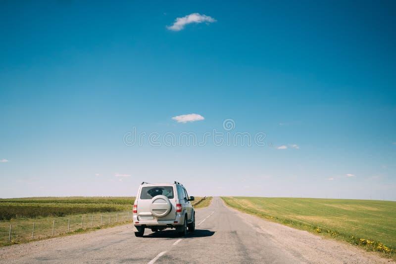 Gråa SUV bilritter längs vägen i landskap för vårsommarfält royaltyfria bilder