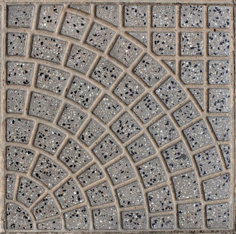 Gr?a tegelplattor f?r fyrkant med den m?nstrade ramen gr? bakgrund som str?s in med sm? svarta kiselstenar av vulkaniskt, vaggar arkivfoton