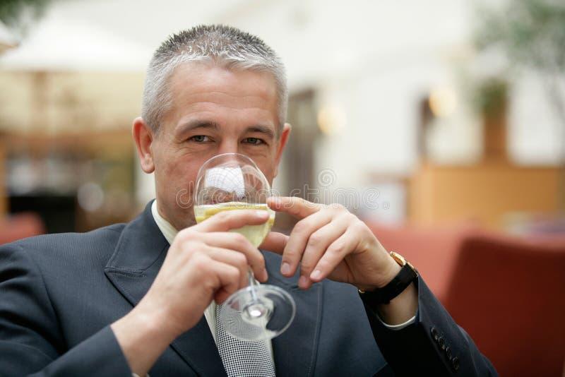 Gråhårig affärsman som dricker vinexponeringsglas av mineralvatten arkivbild