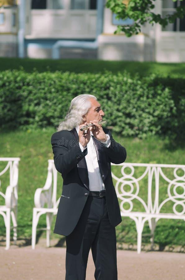 Gråhårig gataflöjtist som spelar flöjten royaltyfri fotografi