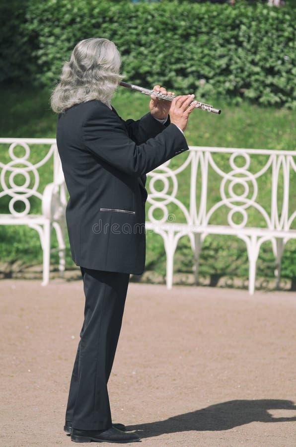 Gråhårig gataflöjtist som spelar flöjten arkivbilder