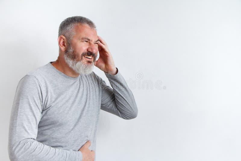Gråhårig man med ett skägg som lider från huvudvärken som är desperat och den belastas, därför att smärta och migrän royaltyfri bild