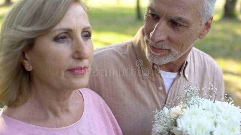 Gråhårig pensionerad man med vita blommor som ser den attraktiva äldre kvinnan royaltyfri bild