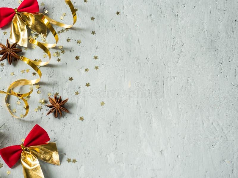 Grånar den dekorativa röda pilbågen för jul och guldbandet på konkret bakgrundscopyspace royaltyfri foto