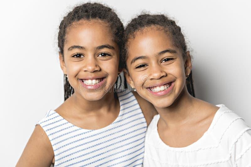 Grånar tvilling- små flickor för förtjusande afrikan på studio bakgrund arkivbild